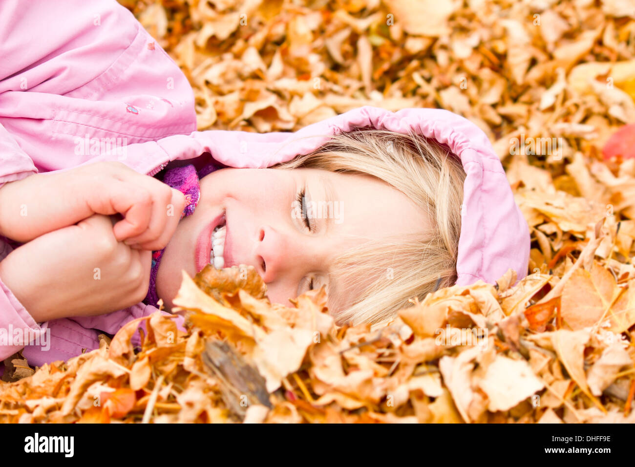Little Girl Lying in Autumn Leaves with a big grin - Stock Image