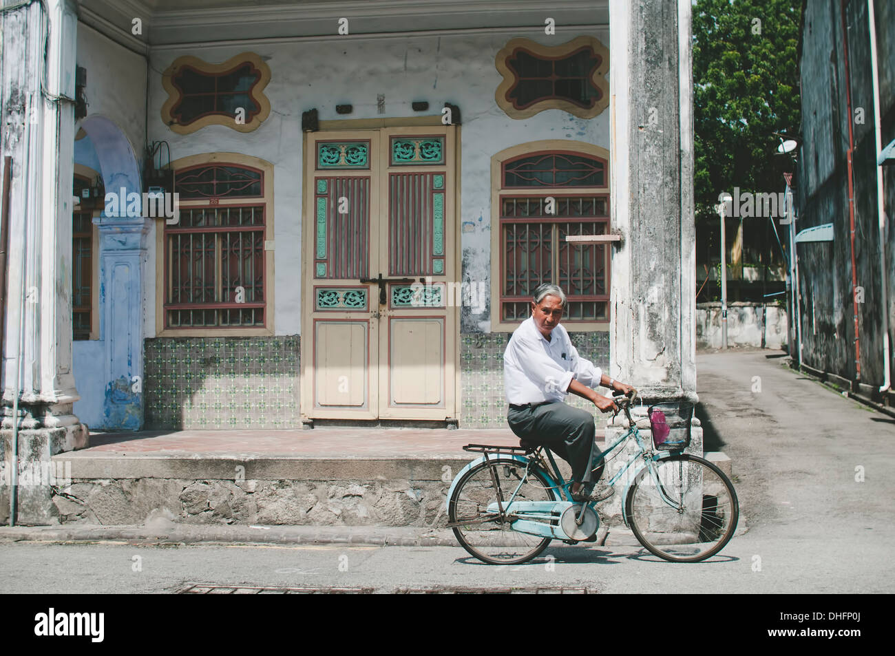 An old man riding a bicycle passing an old shophouse in UNESCO Heritage site, Penang, Malaysia - Stock Image