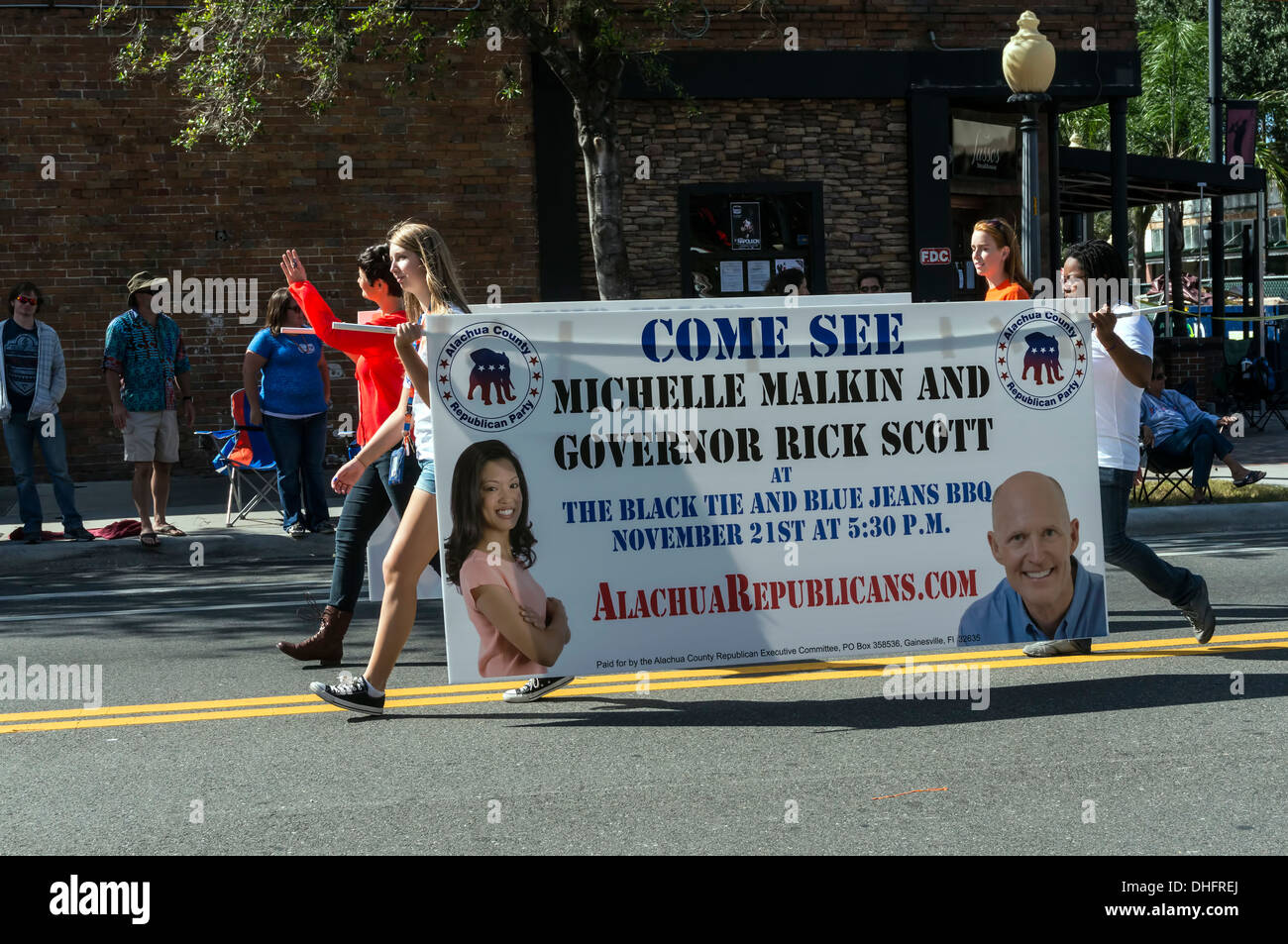 Young Alachua Republicans carry banner announcing black tie and blue jeans BBQ with Michelle Malkin and Governor - Stock Image