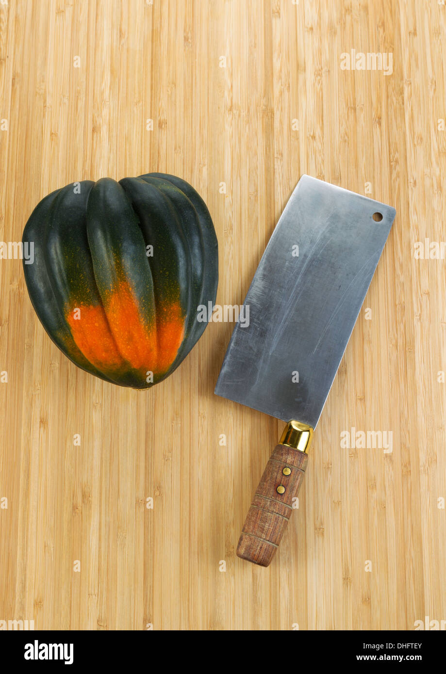 Vertical photo of single large acorn squash with butcher knife on natural bamboo cutting board - Stock Image