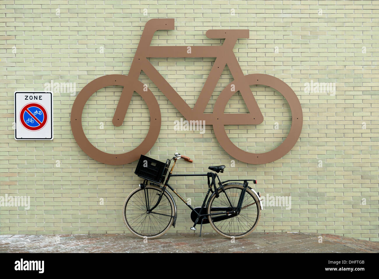 A typical dutch bicycle leant underneath a large bike symbol in Amsterdam, The Netherlands. - Stock Image