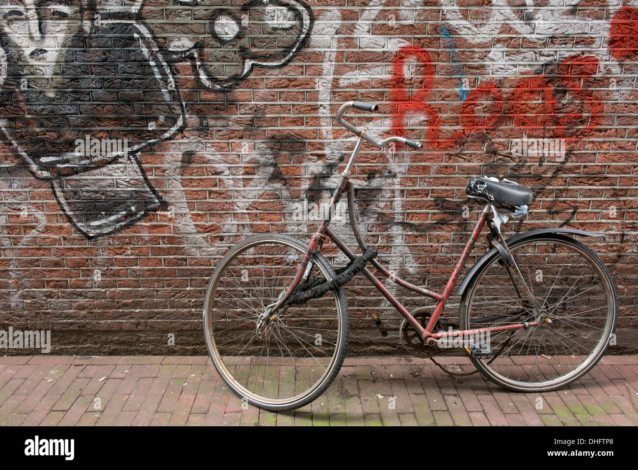 An old bike leant against a graffiti'd wall in the centre of Amsterdam, The Netherlands. - Stock Image