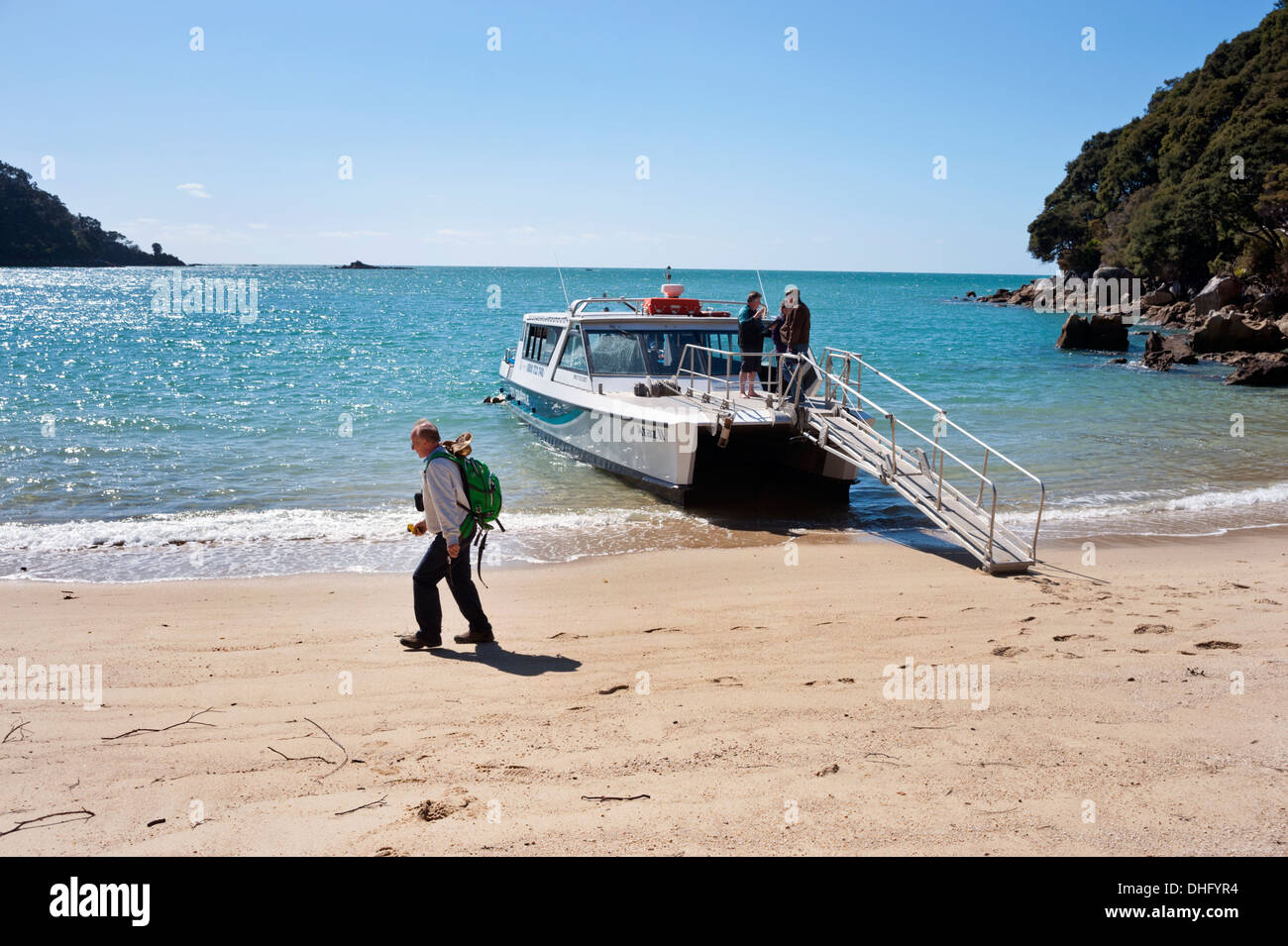 Water taxi serving the Coastal Track in the Abel Tasman National Park, seen at Medlands Bay, South Island, New Zealand. - Stock Image