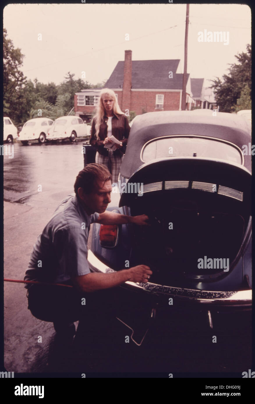 SERVICE STATION MECHANIC ADJUSTS THE ENGINE FOR A YOUNG