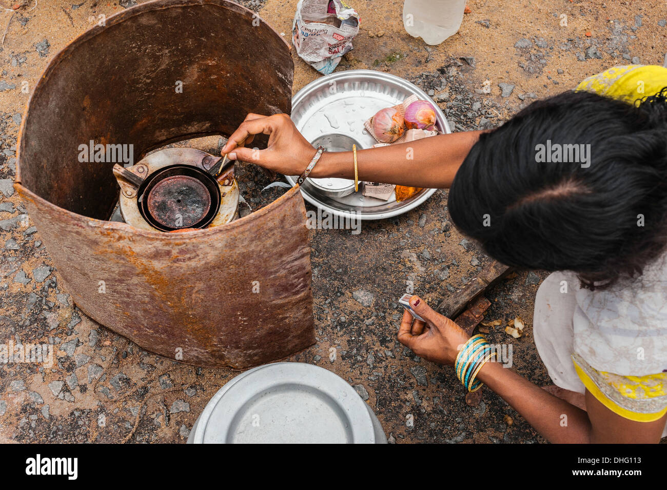 A street dweller prepares to cook a simple meal using primus stove near Kalighat, Kolkata, India. - Stock Image