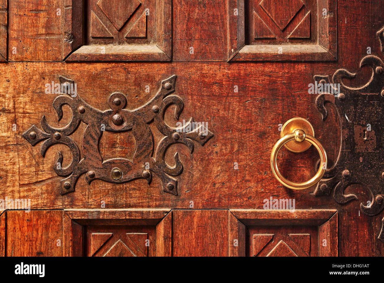 Closeup of old ornate wooden door with a gold door handle in Alba, Italy. - Stock Image