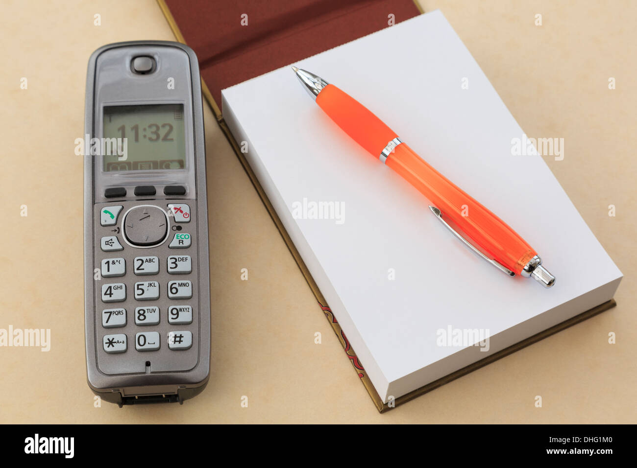 Cordless modern digital telephone handset with a blank notepad notebook and a pen on a plain beige tabletop background - Stock Image