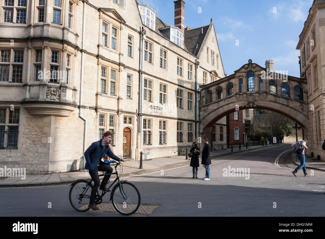 Student cycles past Hertford Bridge, (the Bridge of Sighs) at Oxford University, Oxfordshire, England, GB, UK. - Stock Image