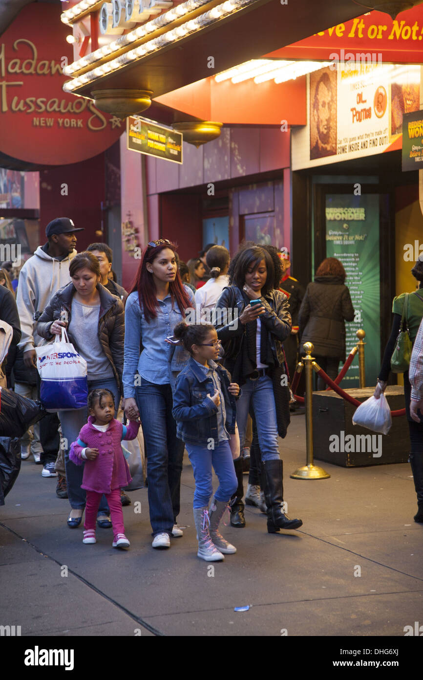 Moms with kids walk by Madame Tussauds on 42nd Street in NYC. - Stock Image
