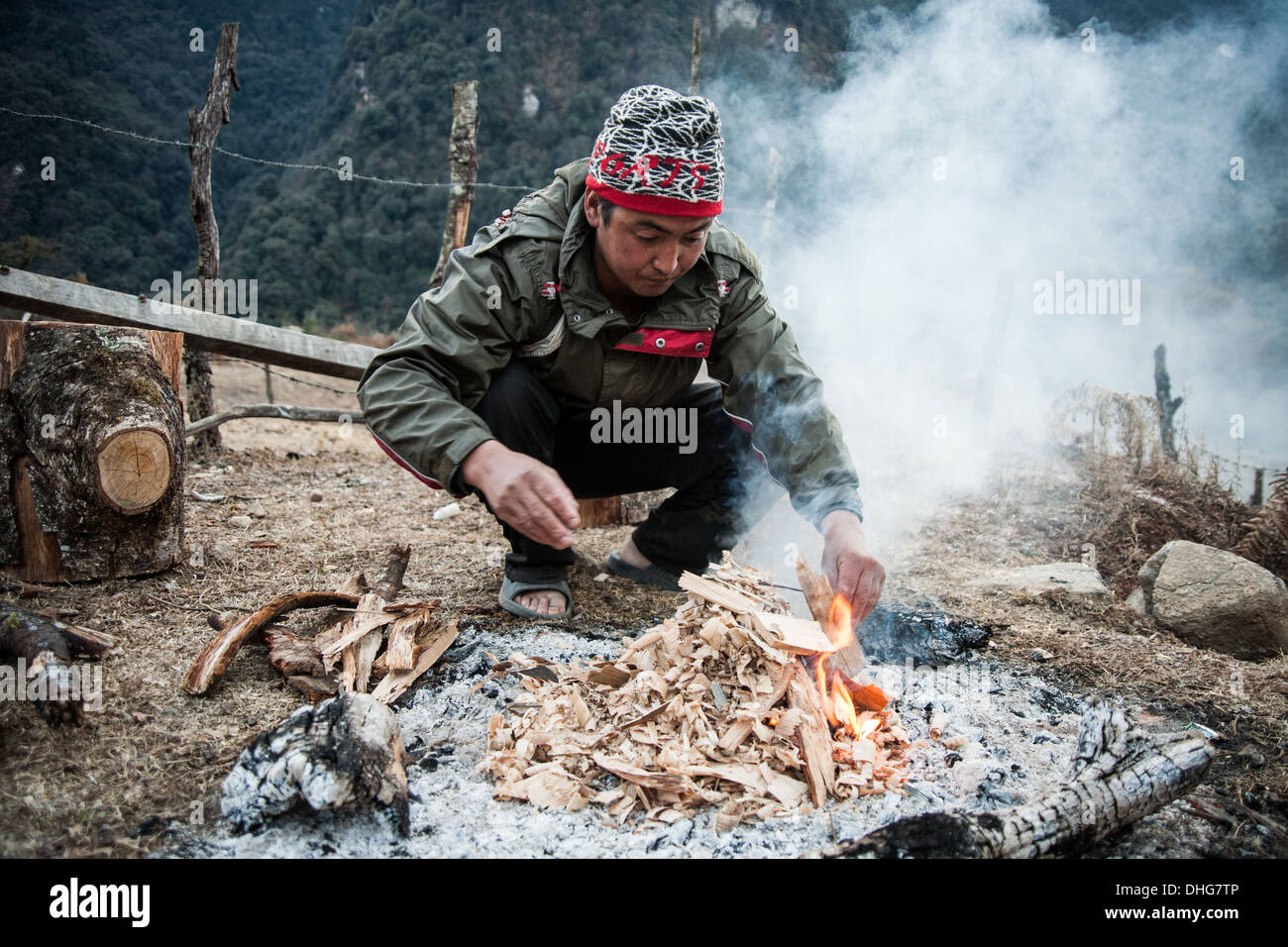 A camp cook starts the fire on a freezing winters night, Gasa - Bhutanese Himalayas - Stock Image