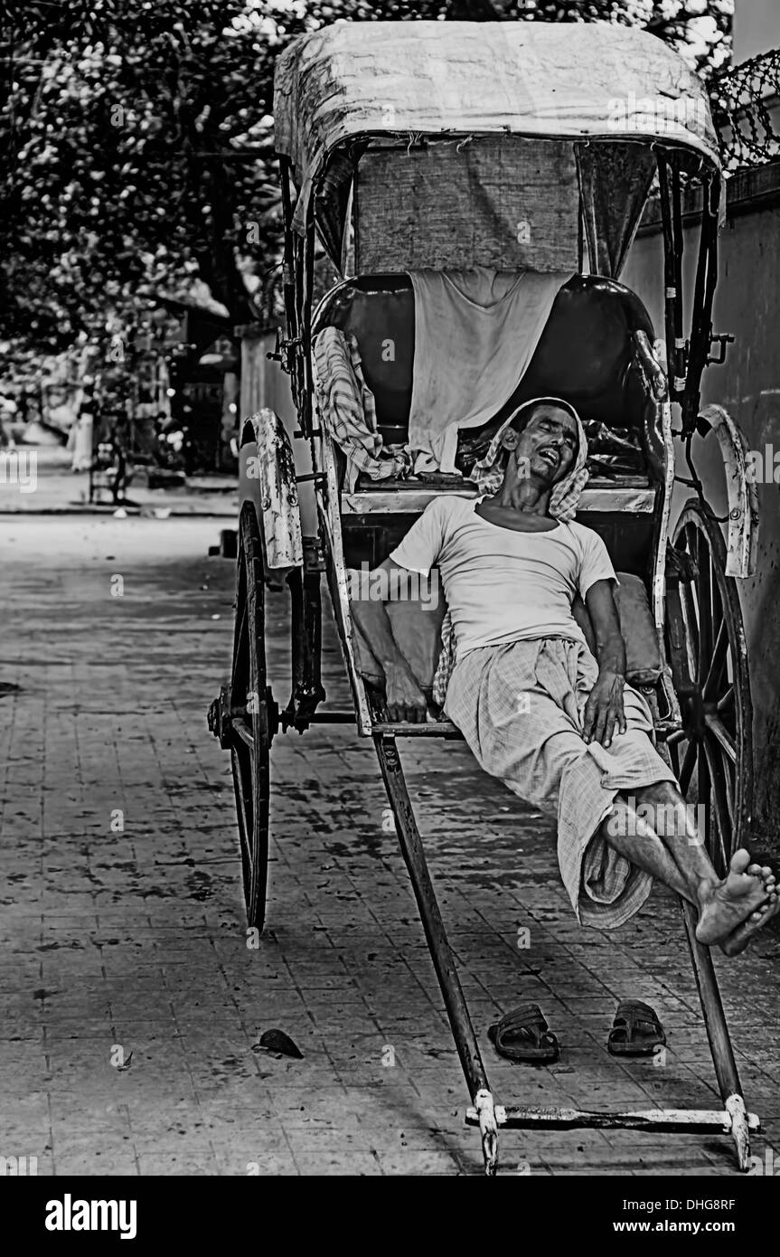 Candid, an old, adult Rickshaw puller taking a afternoon nap, Calcutta, Bengal, India in black and white - Stock Image
