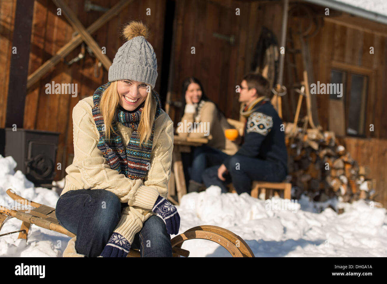 Young woman with friends enjoy weekend break snow winter cottage - Stock Image