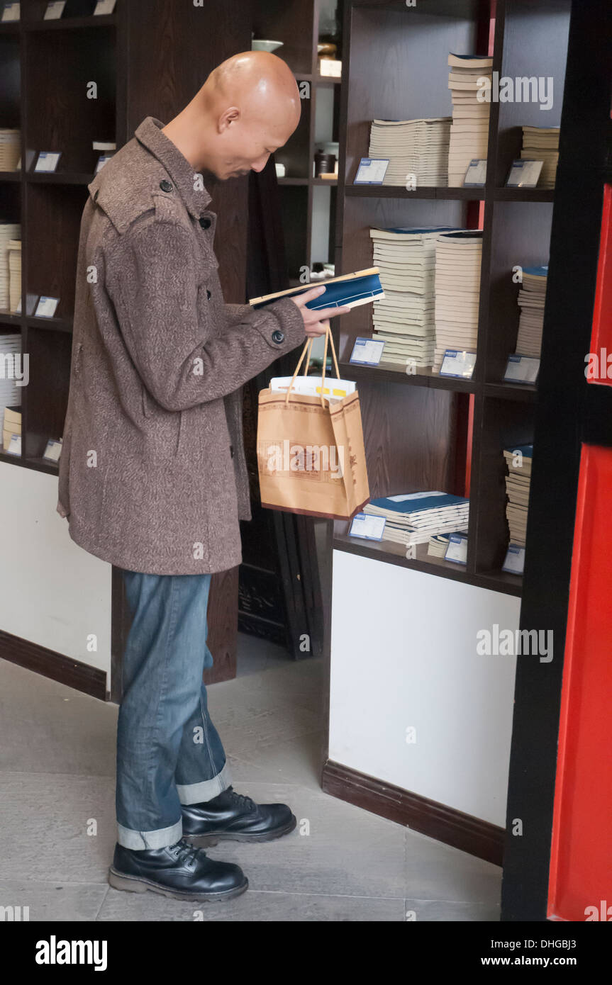 Man browsing the bookstore at Wenhou Buddhist Monastery at Chengdu, Sichuan, China - Stock Image