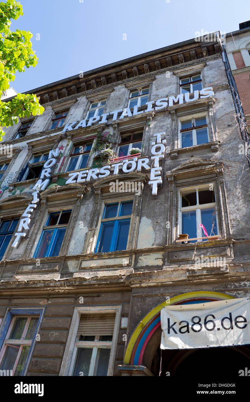 Squat in Prenzlauer Berg with anti-capitalist message on front of building Berlin Germany - Stock Image