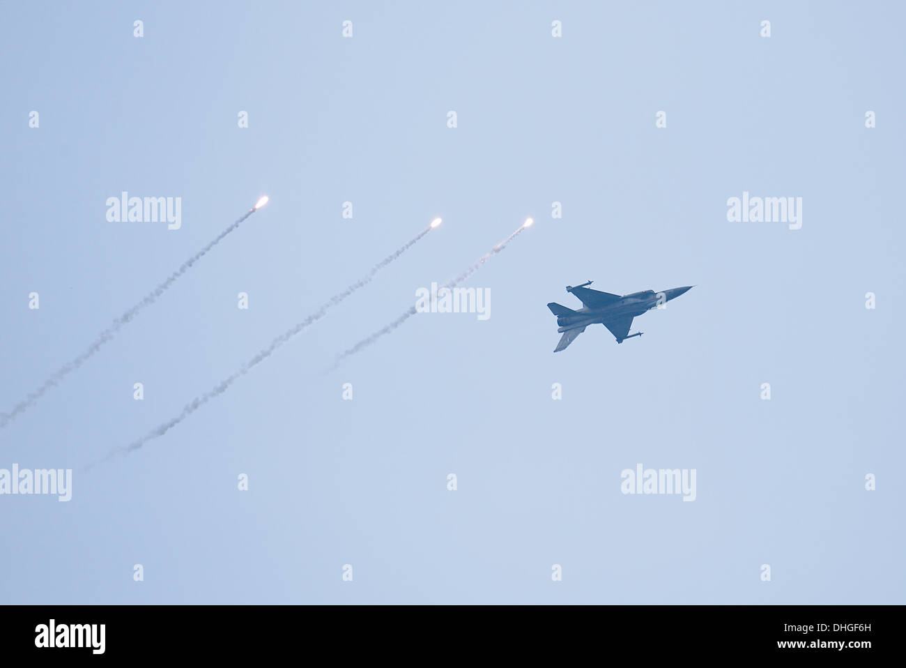 The F-16C throws flares during the air show over Thessaloniki. Due to the annual celebration of the Hellenic Air Force every November, an F-16 Block 52+ belonging to the 'Zeus' acrobat team made an air show at Thessaloniki seaside area. The purpose of the demonstration is people come closer with the Air Force - Stock Image