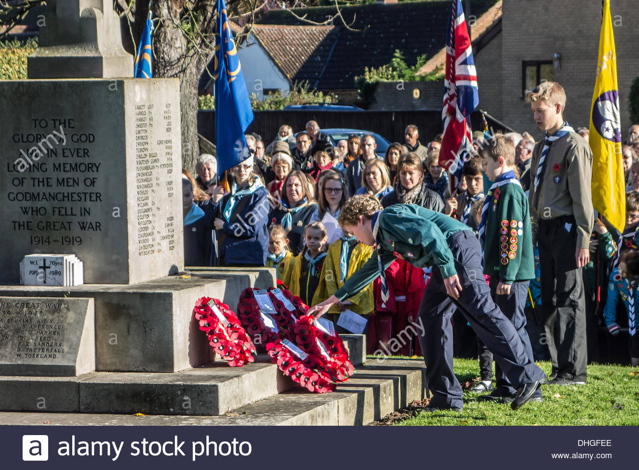 Scouts lay a poppy wreath at the war memorial in Godmanchester, Cambridgeshire, England on the 10th November 2013 at the annual remembrance service in the town. - Stock Image