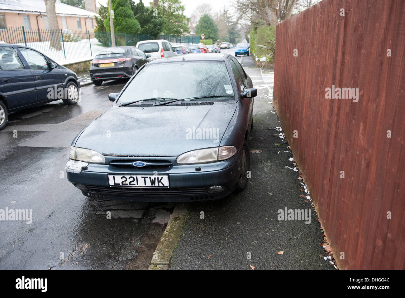 Illegally parked car on pavement blocking sidewalk Stock Photo