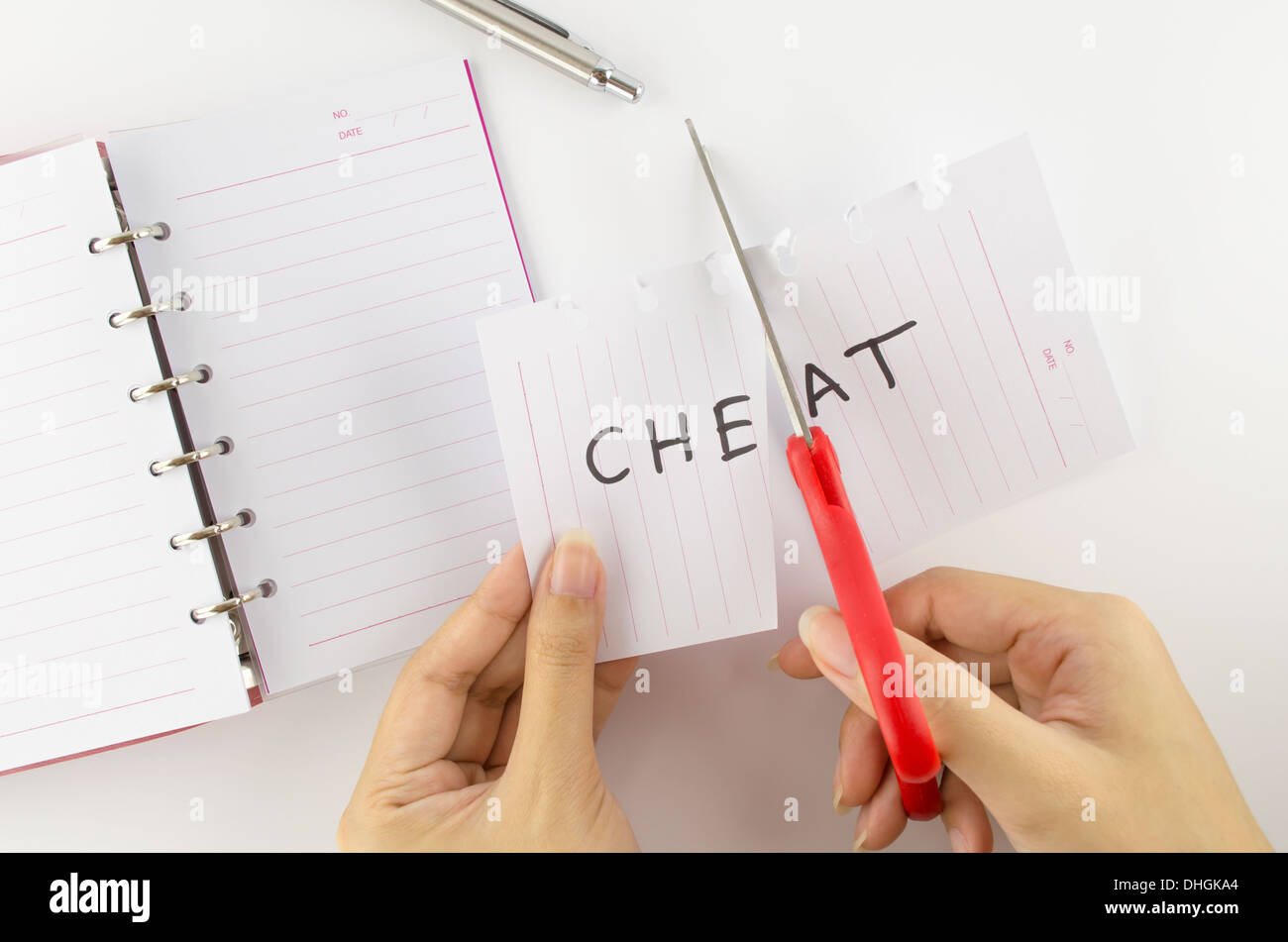 Persons who were cutting paper labeled 'cheat' - Stock Image