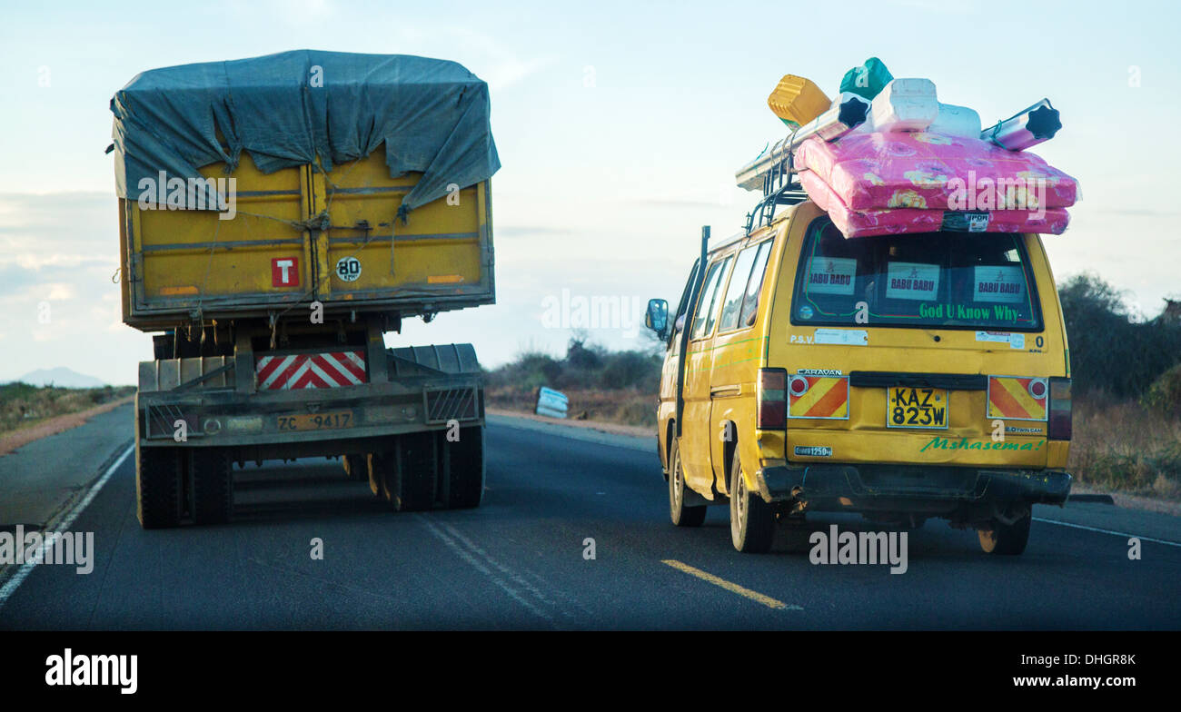 A heavily laden matatu taxi overtakes a lorry on the Nairobi Mombasa road in Kenya - Stock Image
