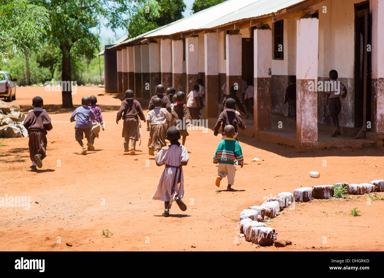 primary school children running to classrooms in a school near Voi in Southern Kenya - Stock Image