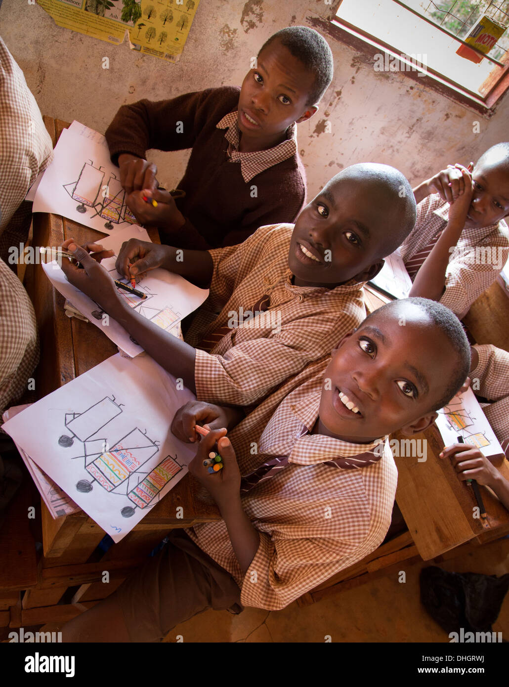 Schoolboys in a Kenyan classroom show off their art works - Stock Image