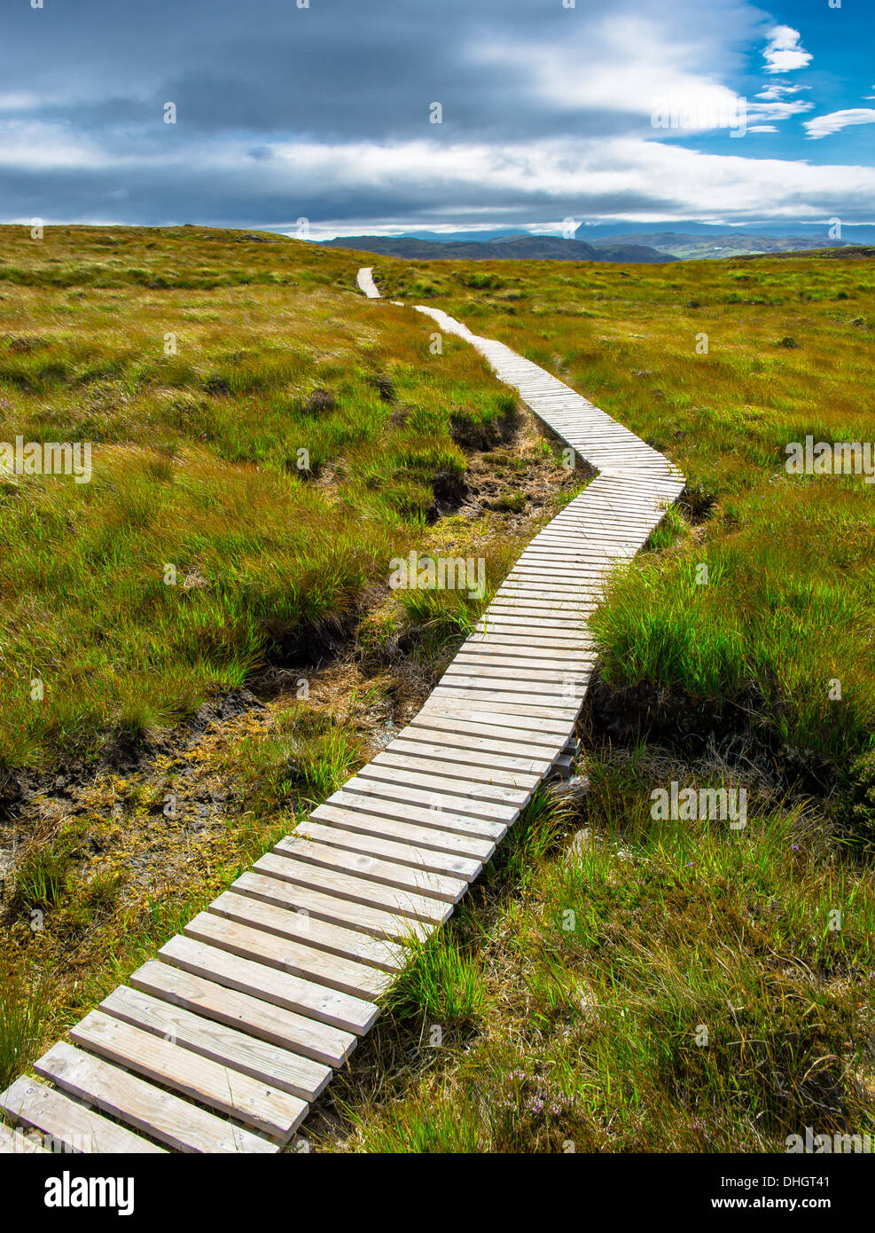Narrow path up a hill toward the cloudy sky - Stock Image