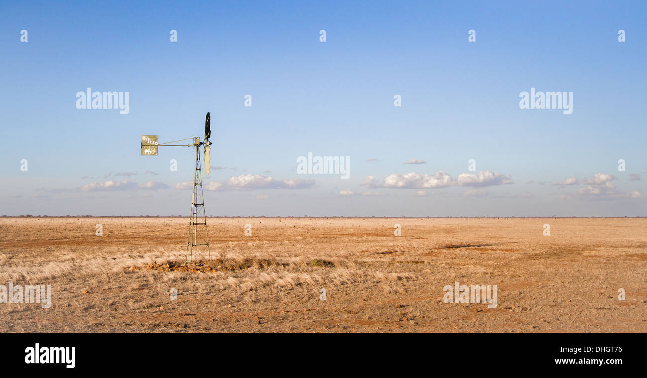 Isolated wind pump feeding a waterhole in the parched savanna grassland of Tsavo East National Park in southern Kenya - Stock Image