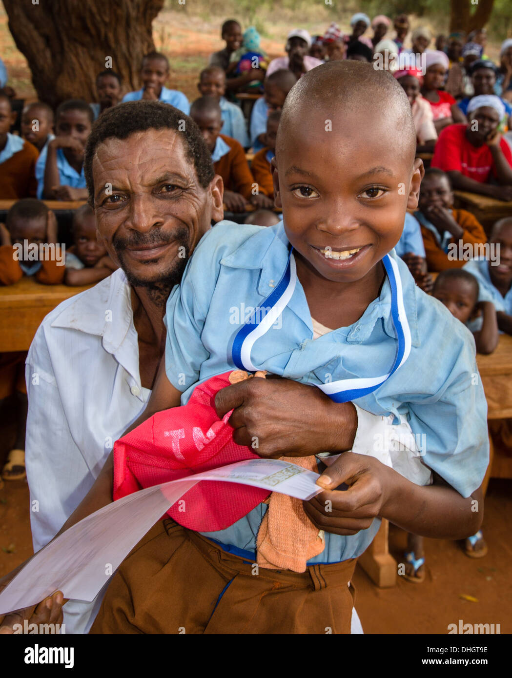A proud father lifts his child up for a photograph in a village school near Voi Southern Kenya - Stock Image