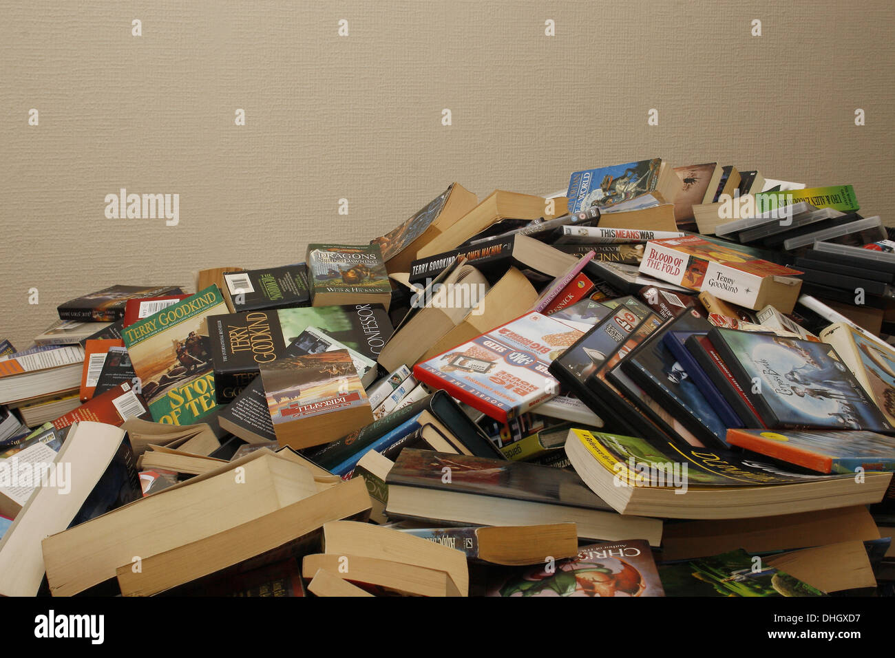 Large pile of books and DVDs on floor of house - Stock Image