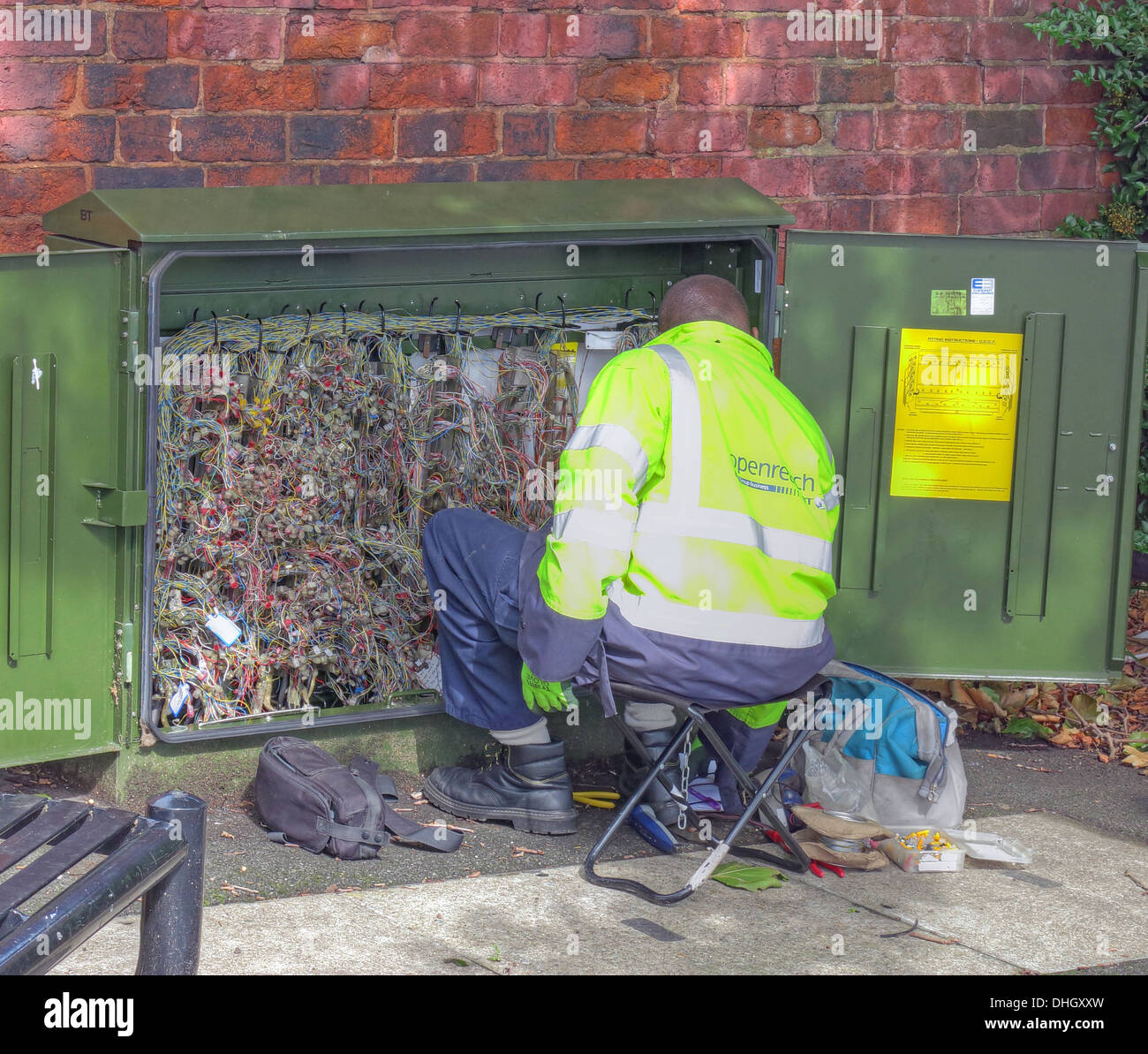 BT Openreach telecoms engineer fixing fault in green roadside box - Stock Image