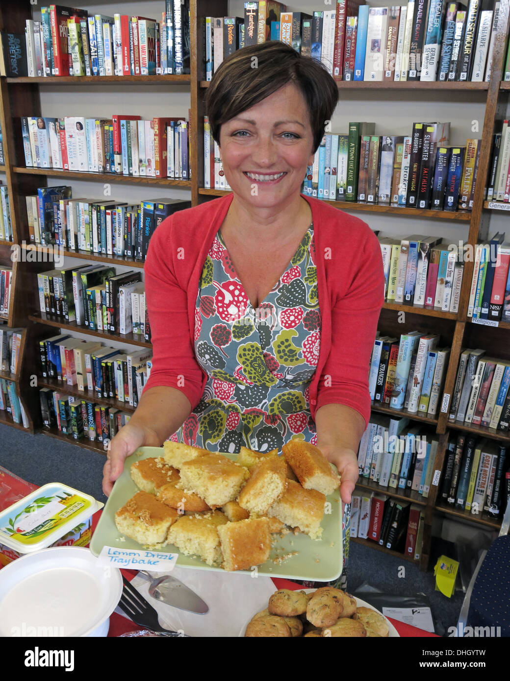 Community Library volunteer offers cakes Grappenhall Warrington Cheshire England UK - Stock Image