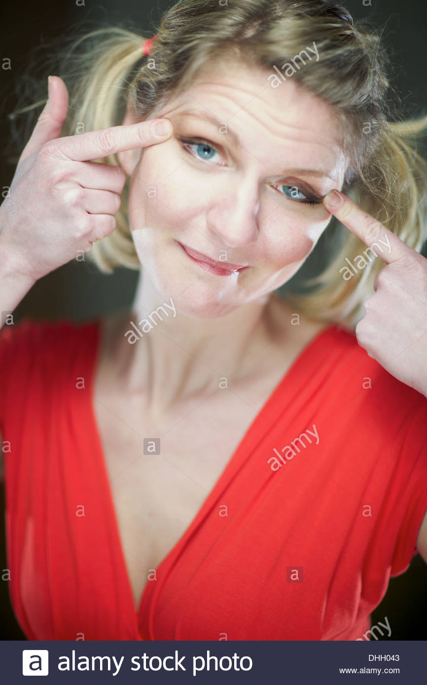 Politically incorrect German woman makes 'chinky eyes' at the behest of the obviously intoxicated irresponsible photographer. - Stock Image