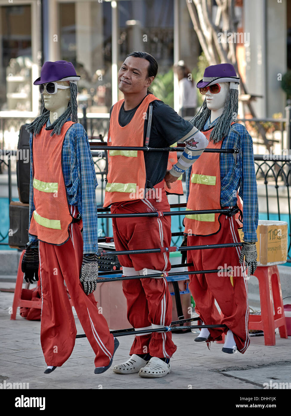 Street entertainer with synchronized mannequins preparing to perform a dance routine. Thailand S. E. Asia. - Stock Image