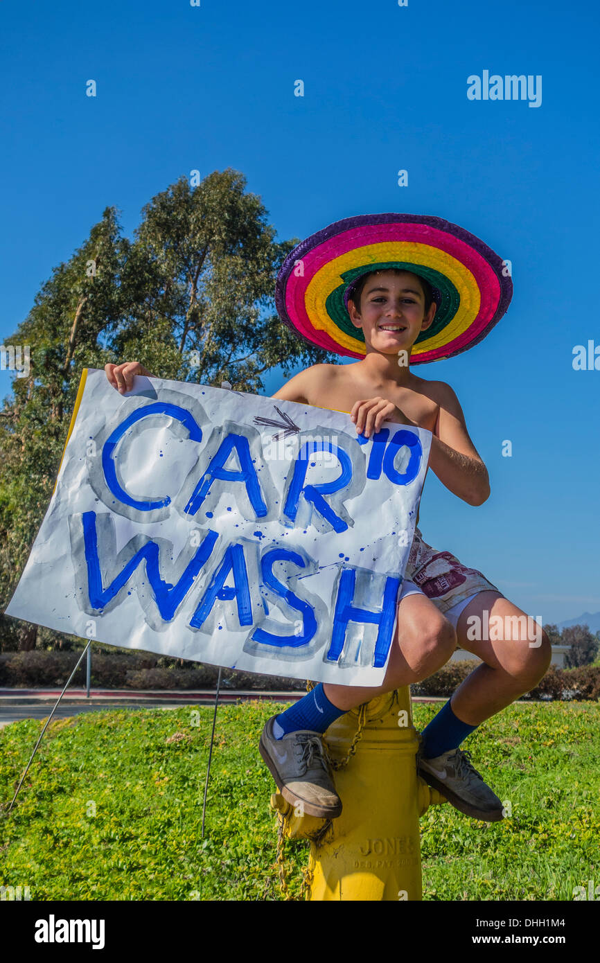An 8-10 year old boy holds a car wash sign while straddling a fire hydrant and wearing a multi-colored sombrero. - Stock Image