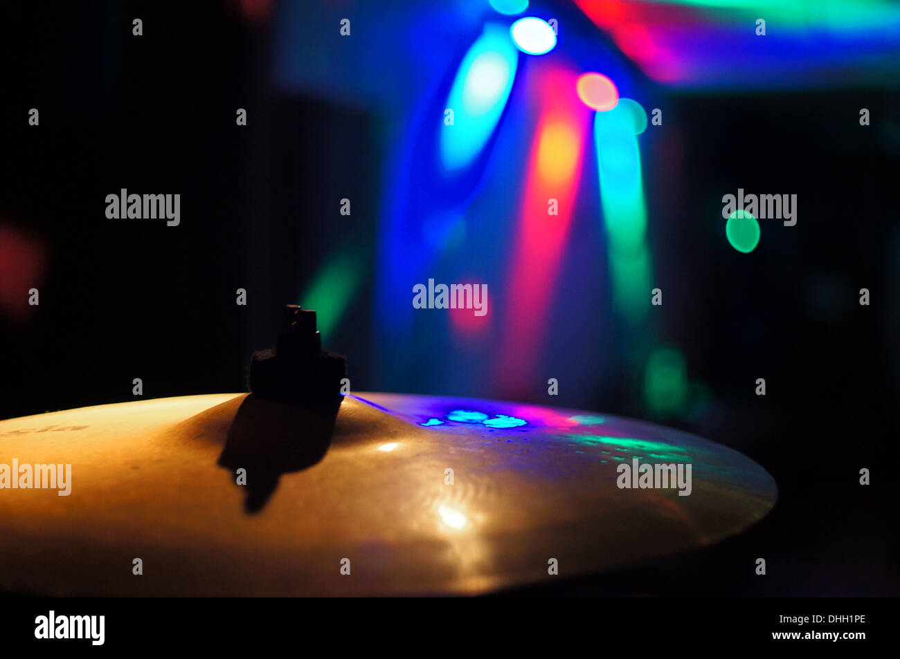 A cymbal and coloured lights in a dark bar Stock Photo