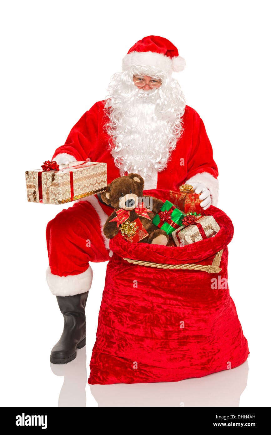 Santa Claus or Father Christmas handing out gifts from his sack ...