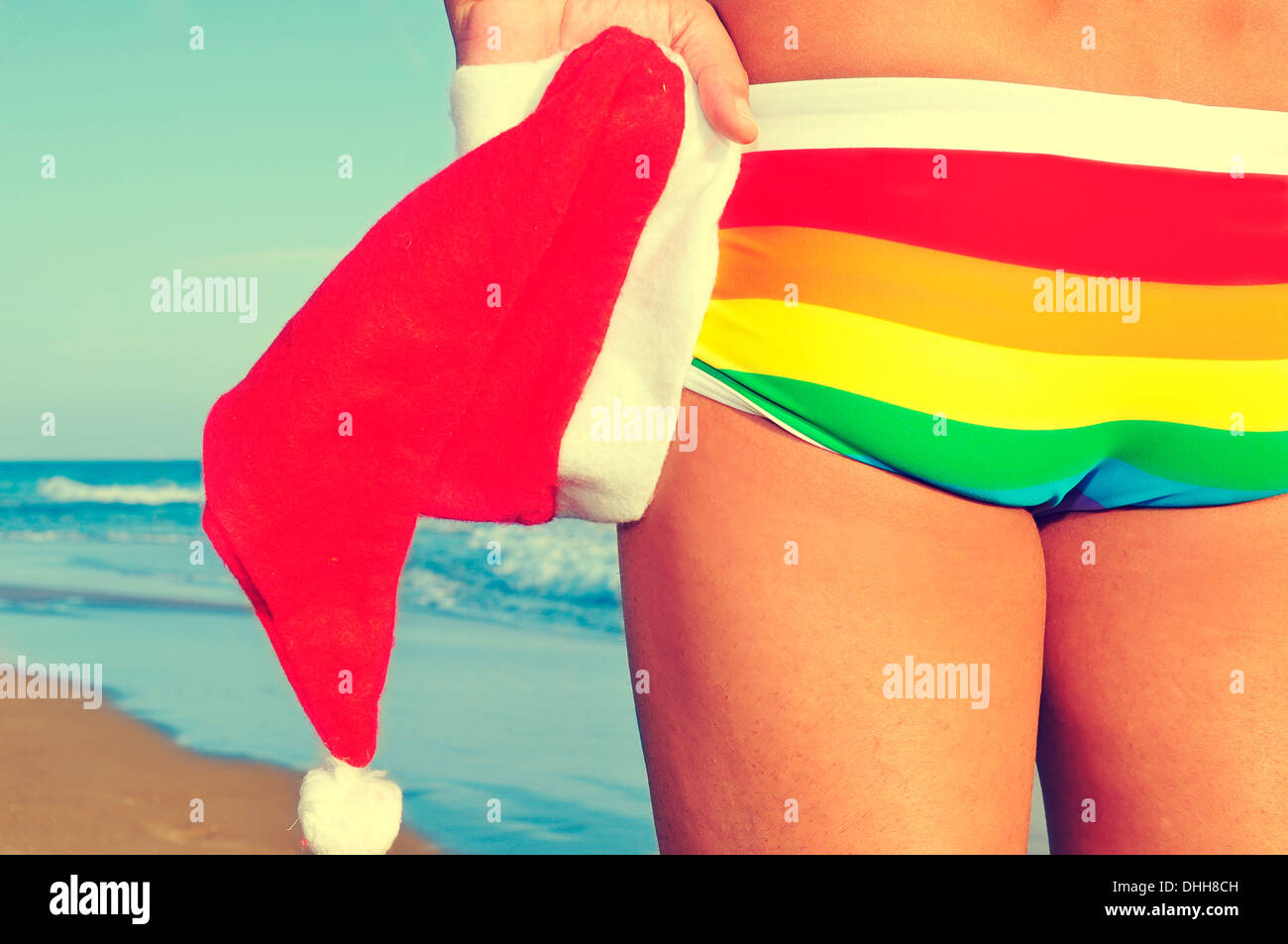 someone at the beach wearing a rainbow swimsuit and holding a Santa hat in his hand - Stock Image