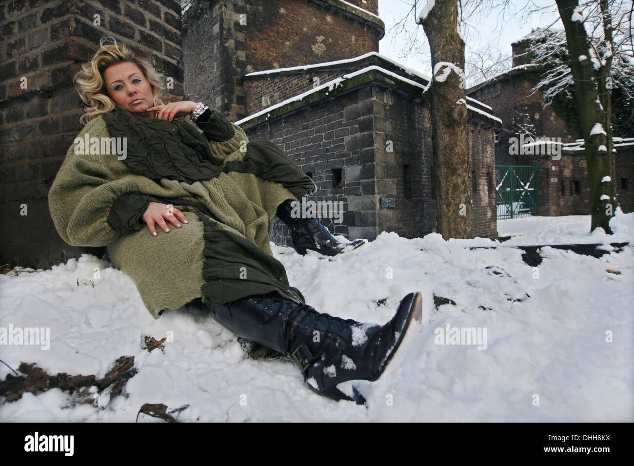 blond woman in a green coat Stock Photo