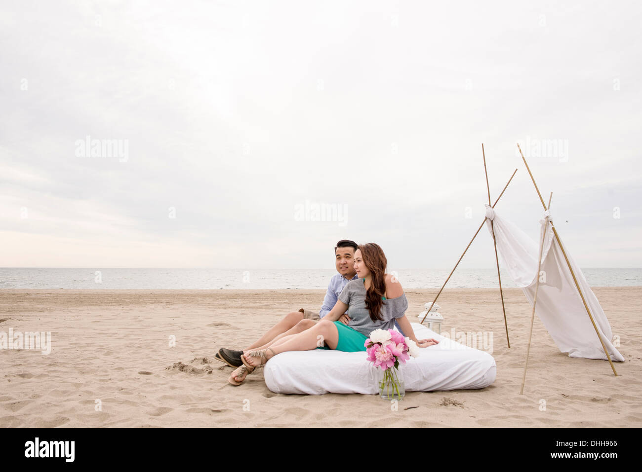 Young couple sitting on mattress canopy on beach - Stock Image