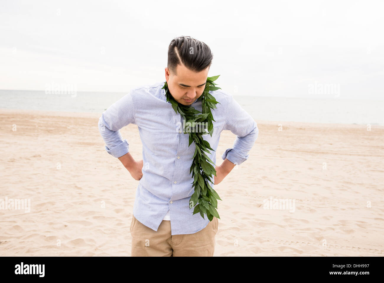 Man standing on beach with foliage round his neck - Stock Image