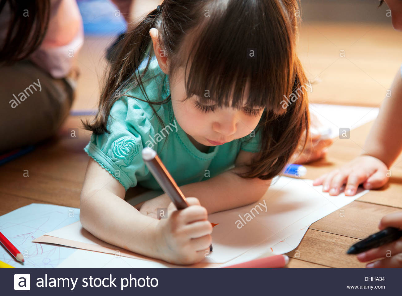 Girl lying on floor drawing - Stock Image