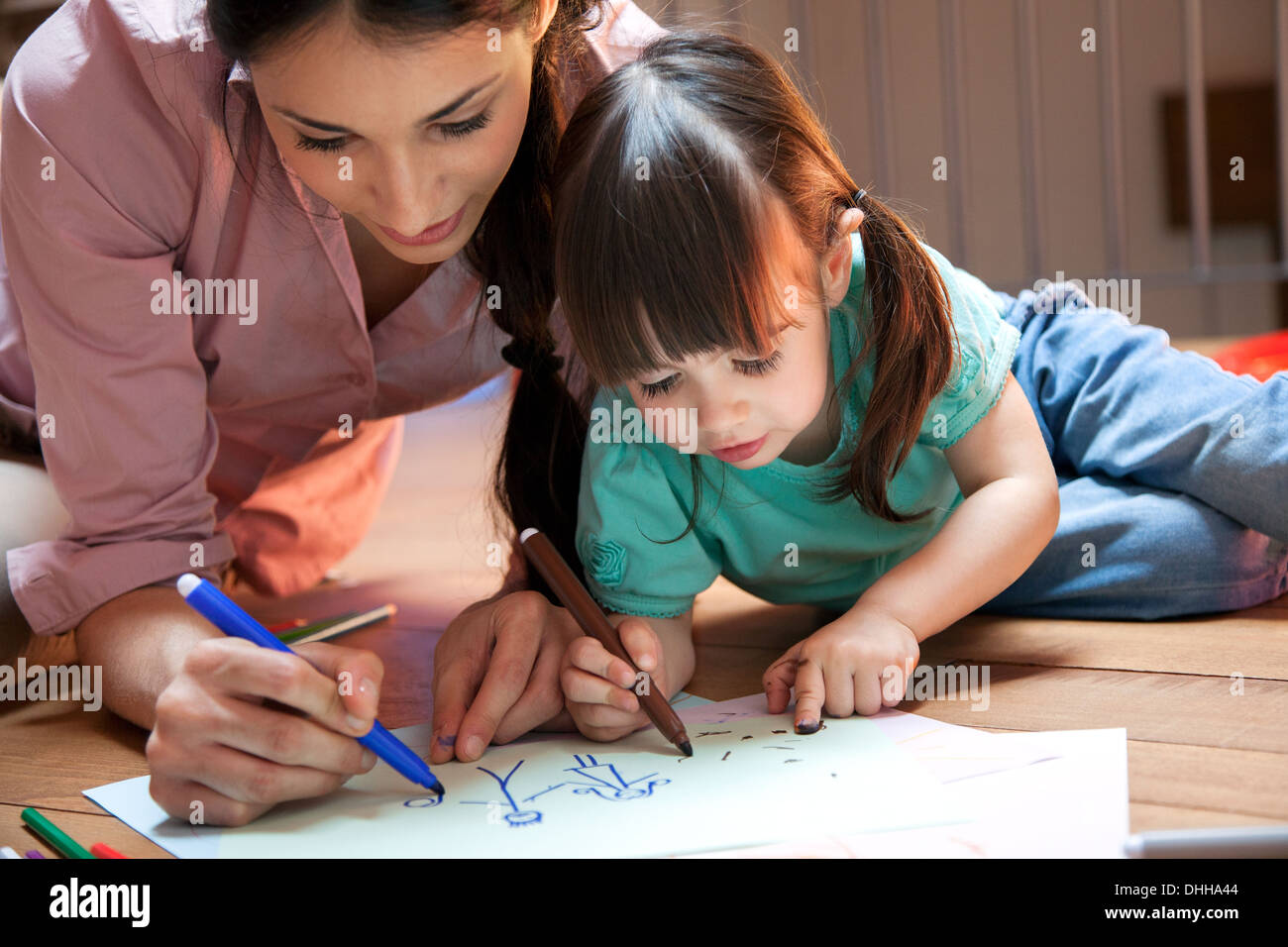 Mother and daughter lying on floor drawing - Stock Image