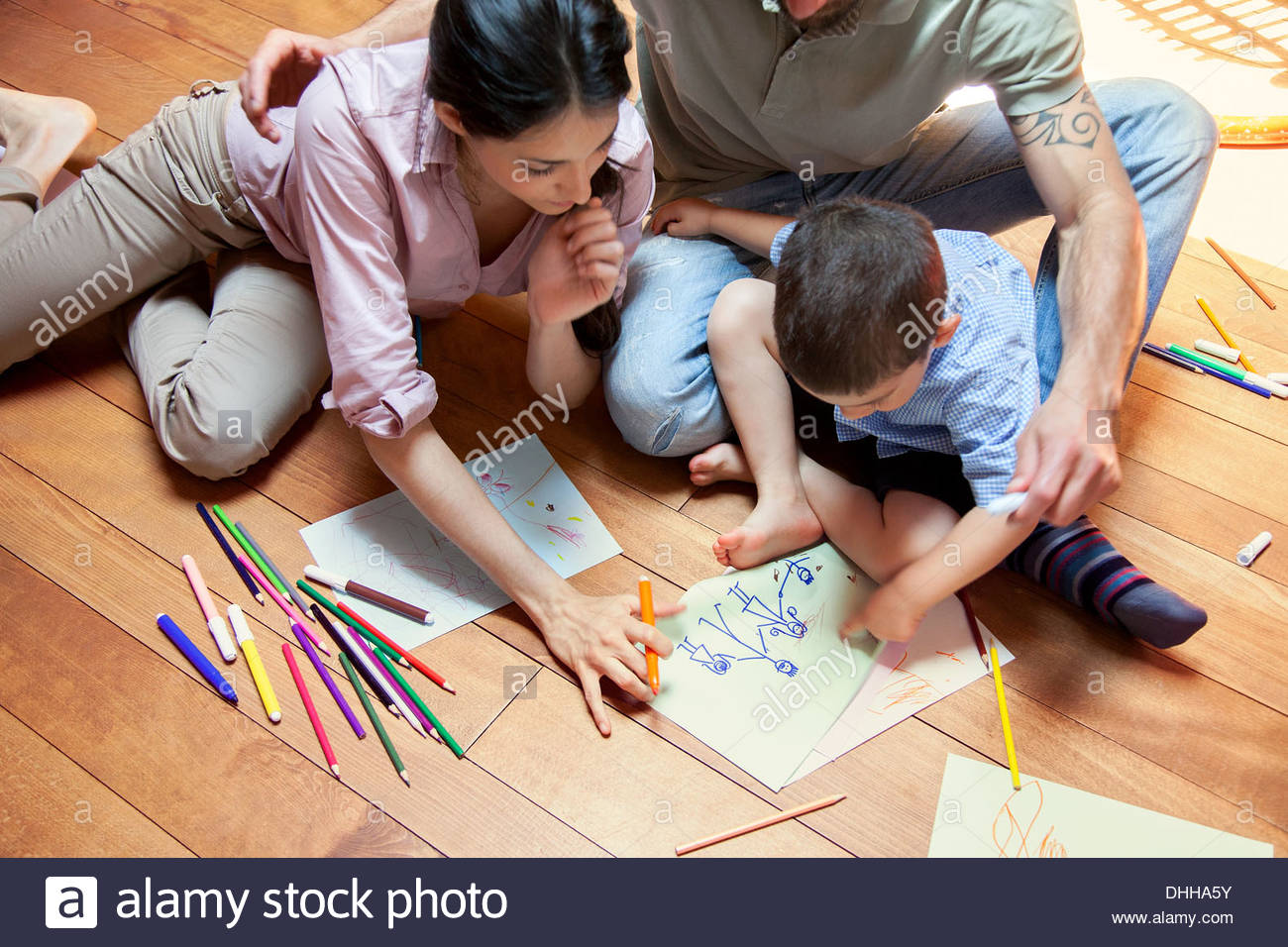 Boy sitting on floor drawing with parents - Stock Image