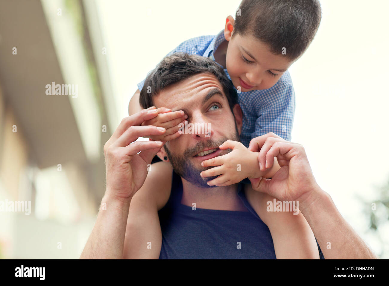 Father carrying son on shoulders, boy covering man's eye - Stock Image