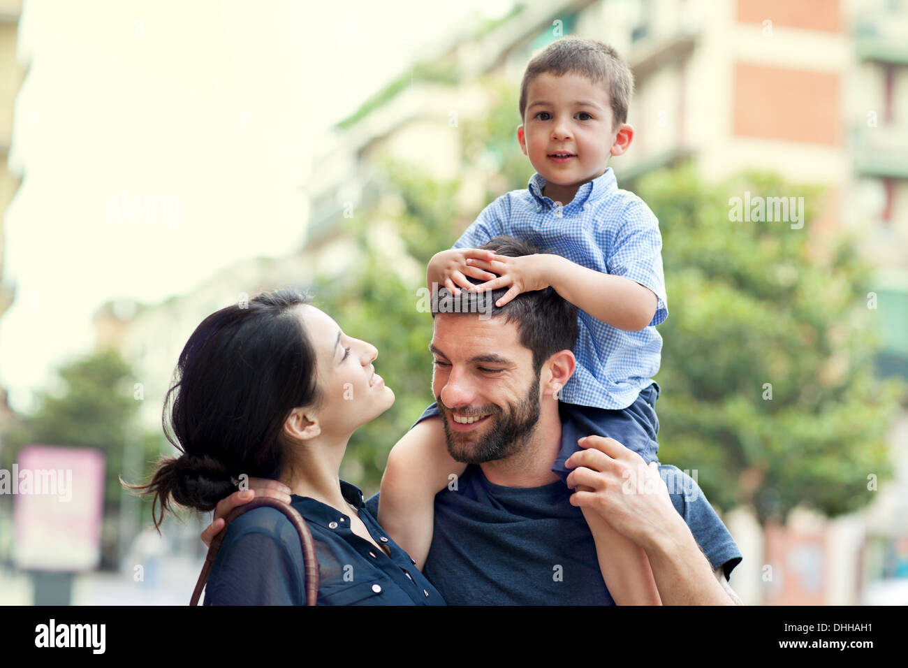 Father carrying son on shoulders with woman - Stock Image