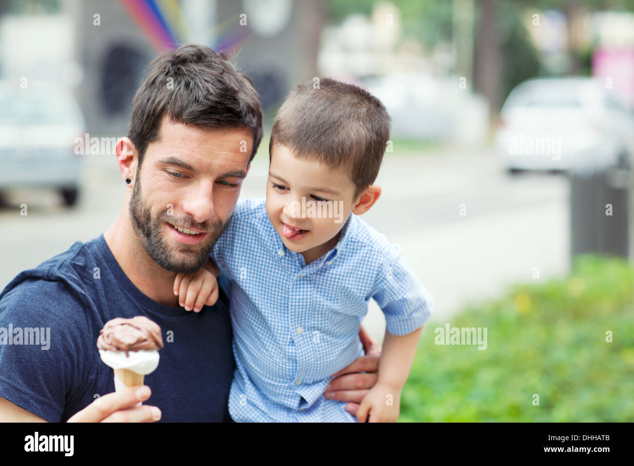 Father holding ice cream, son licking lips - Stock Image