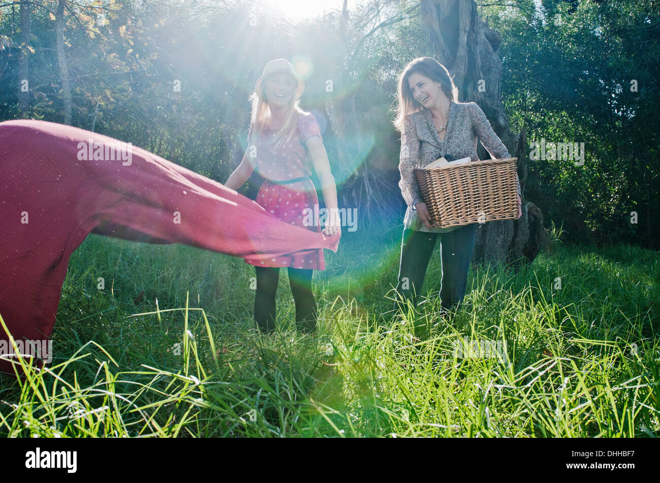 Young women laying out picnic blanket - Stock Image