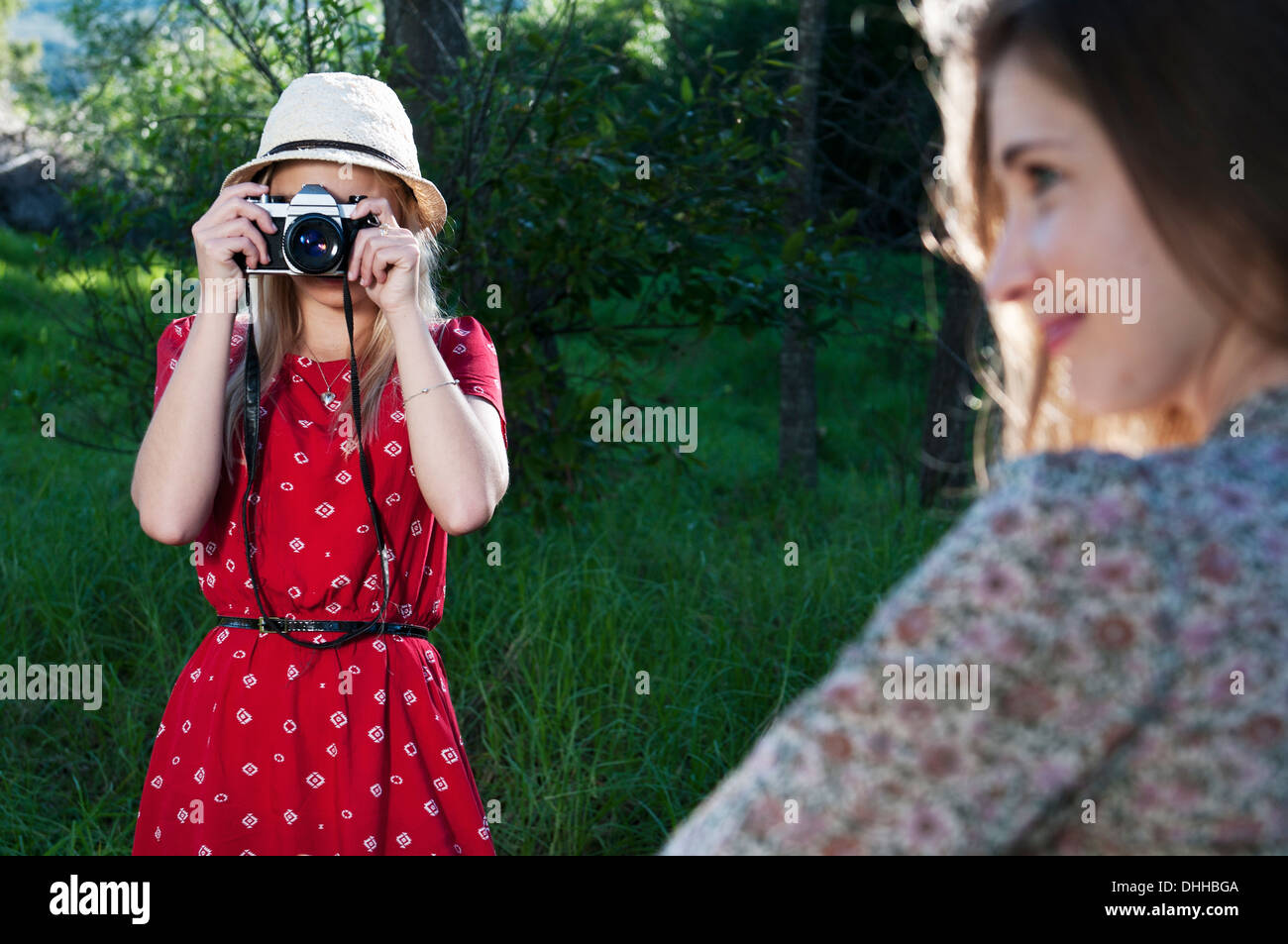 Young woman taking photograph of friend - Stock Image