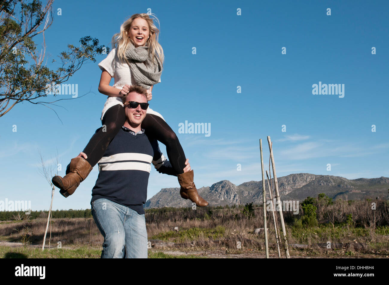 Young womans sitting on boyfriend's shoulders - Stock Image