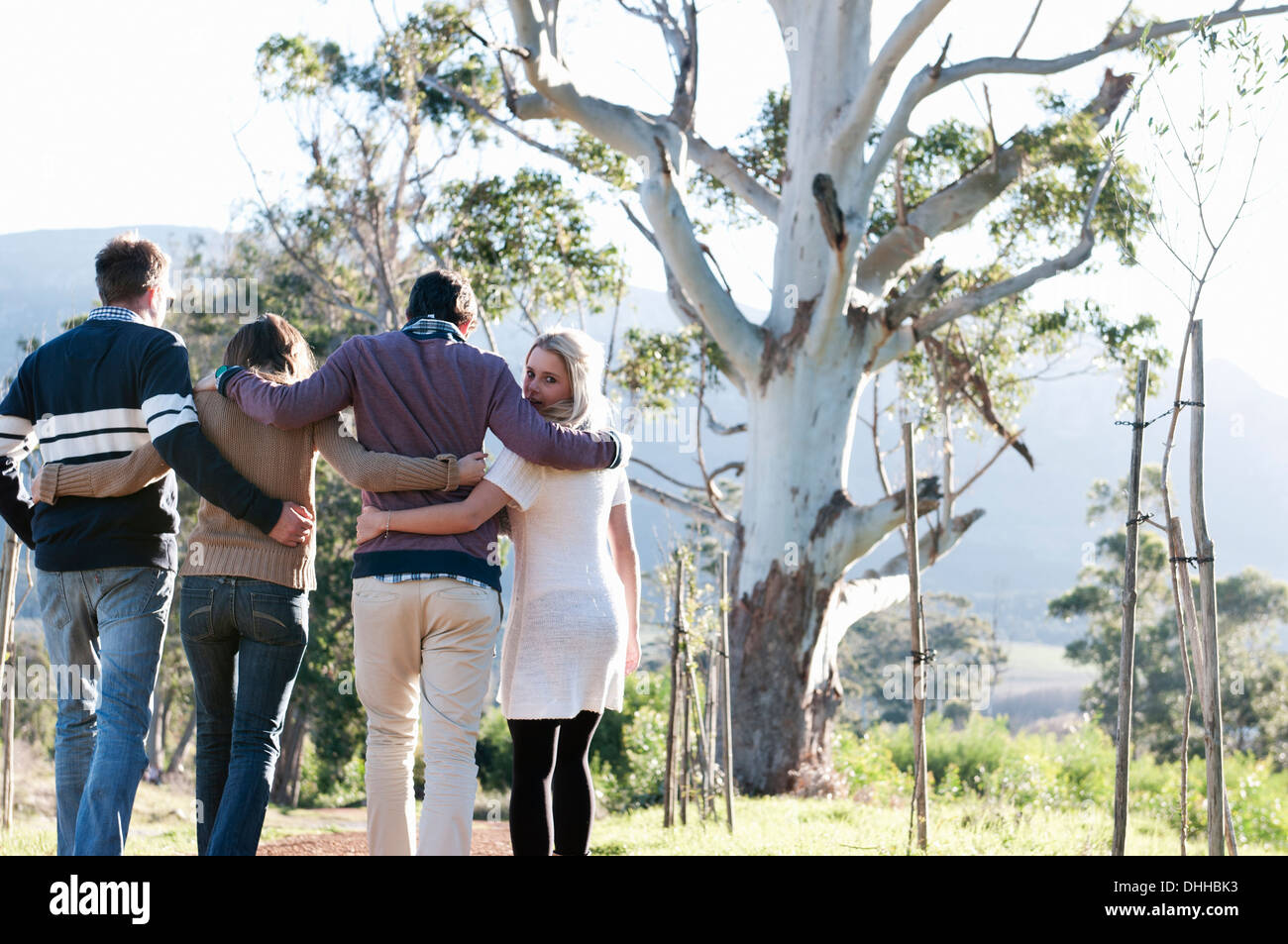 Friends walking through countryside with arms around Stock Photo
